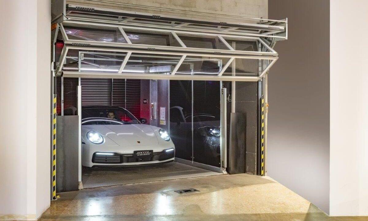Porsche sort de l'ascenseur de voiture qui est verrouillé avec des portes Compact